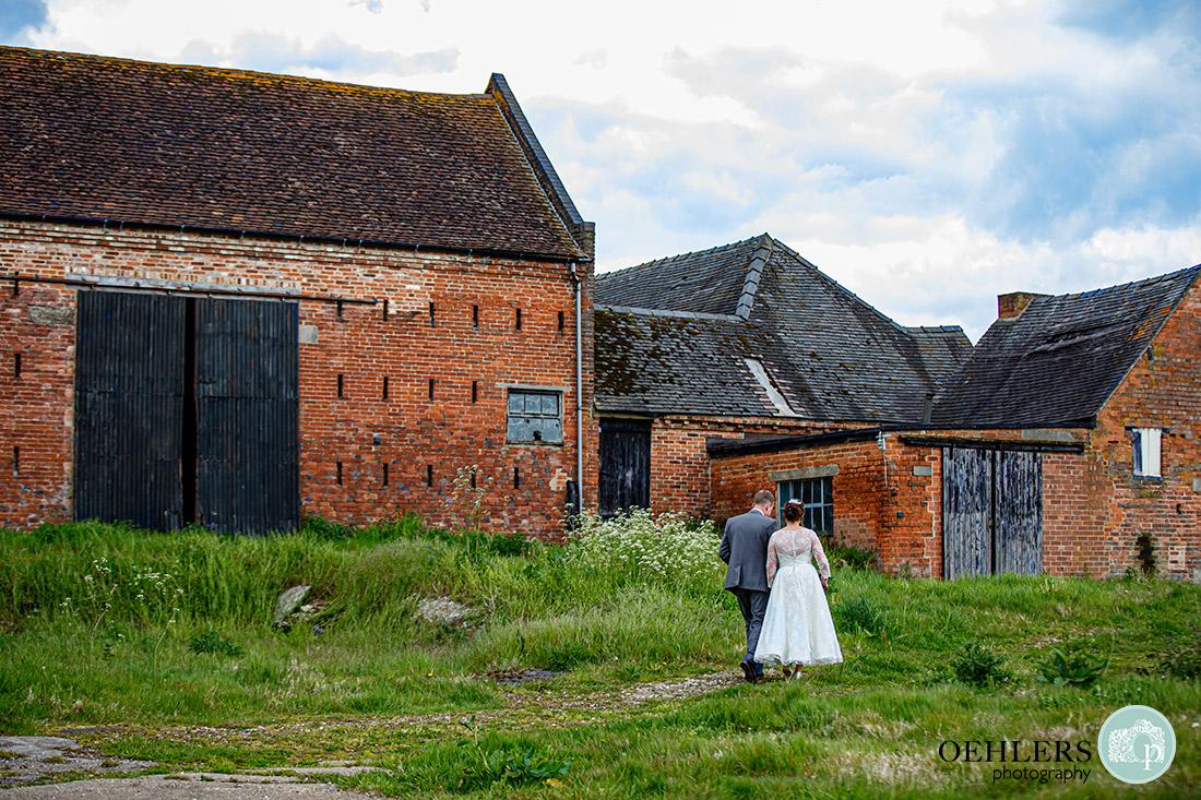 Kedleston Country House Photographers - walking away from camera towards rustic barns.