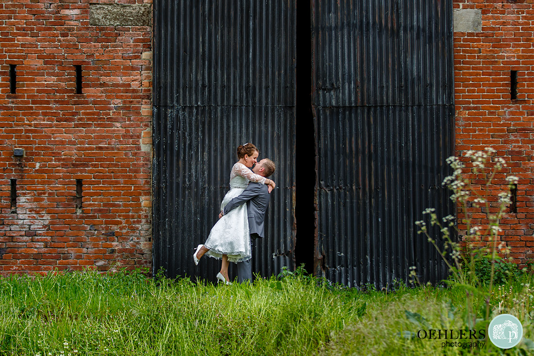 Kedleston Country House Photographers - grrom picks up the bride in front of black gates.