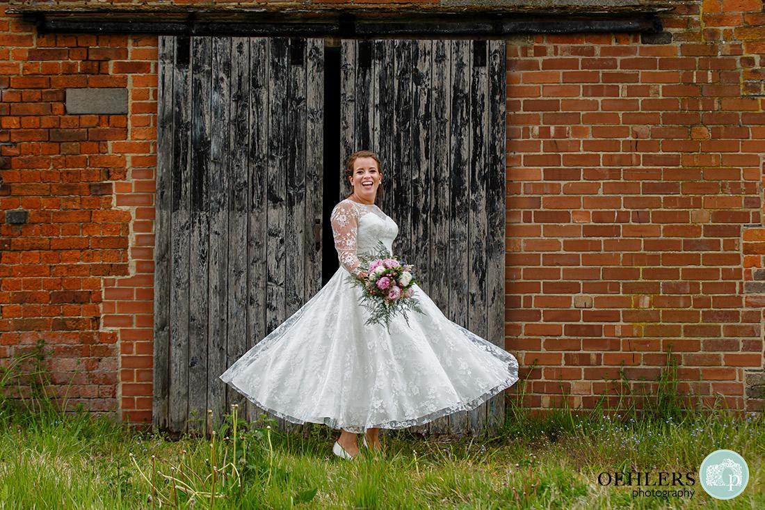Bride twirling her dress in front of black gates.