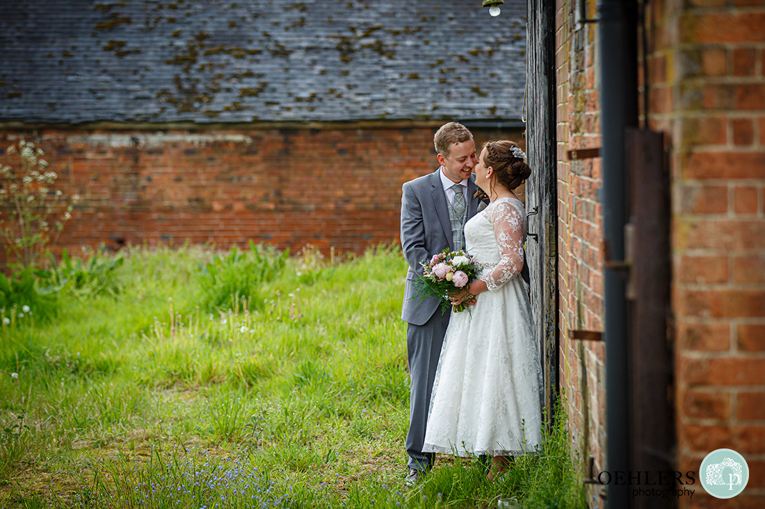 Kedleston Country House Photographers - a ramntic kiss by the wall of the rustic barn.