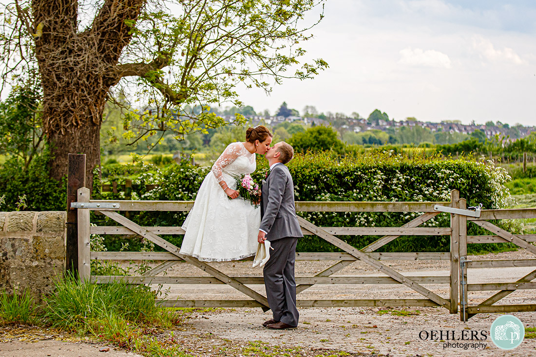 Kedleston Country House Photographers - bride sitting on a gate kissing the groom who is standing.
