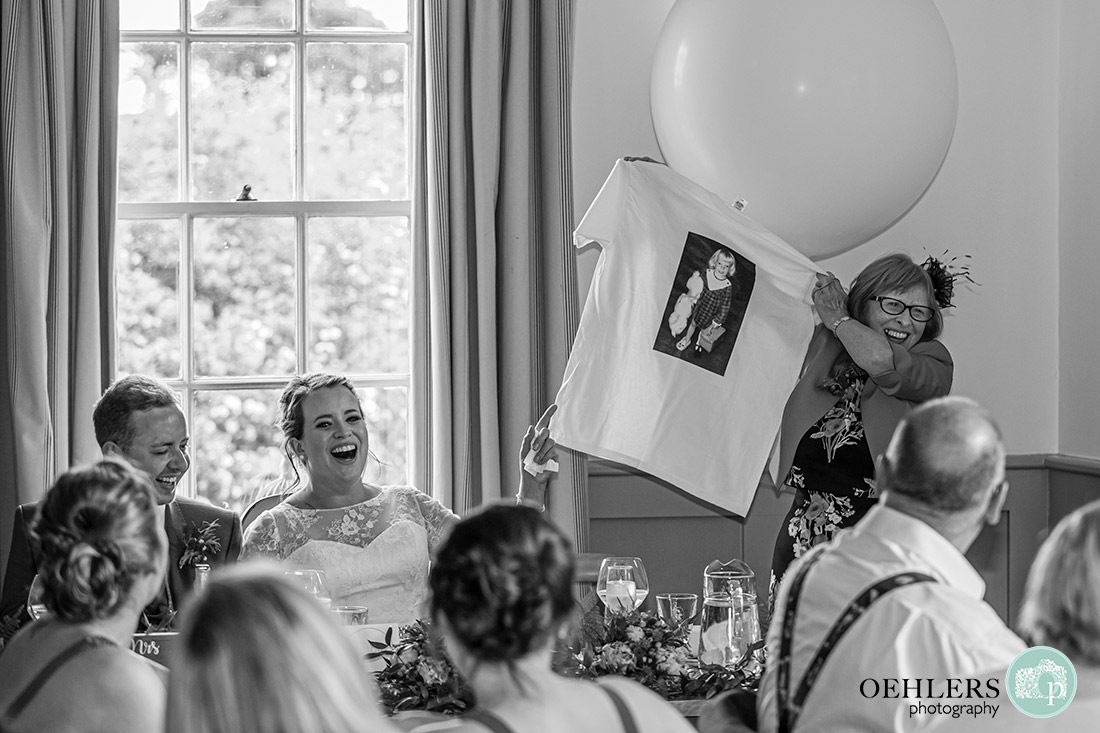Kedleston Country House Photographers - bride's mum holding a T-shirt with picture of bride. Bride and Groom laughing.
