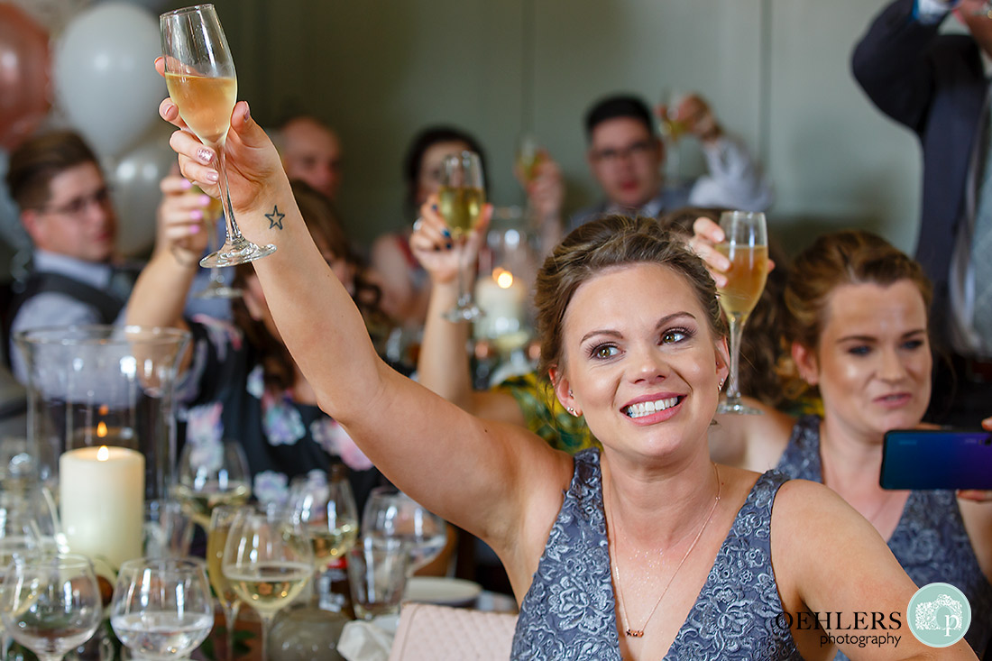 Kedleston Country House Photographers - bridesmaid toasting the bride and groom.