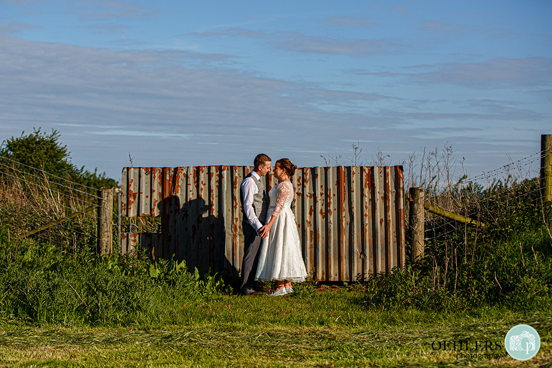 Couple in front of a corrugated fence.