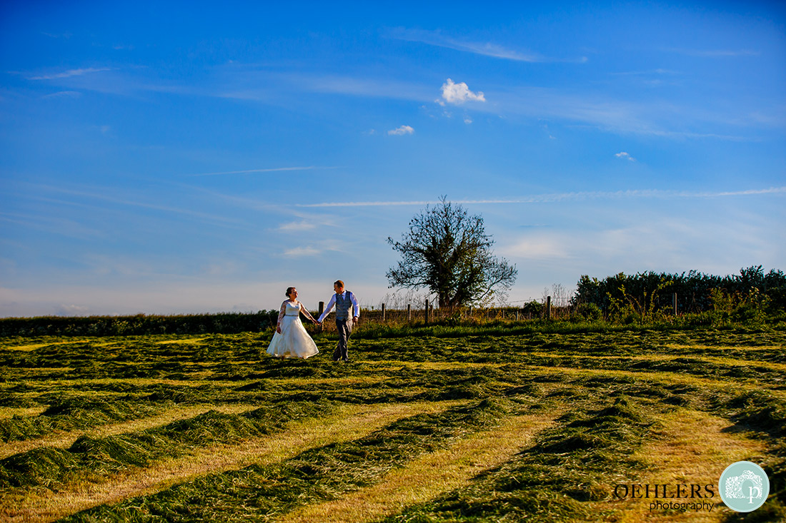 Kedleston Country House Photographers - bride and groom walking hand in hand through newly mown field.