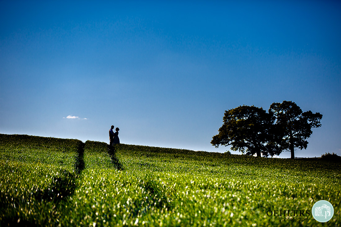 Kedleston Country House Photographers - silhouette of bride and groom at the top of a field.
