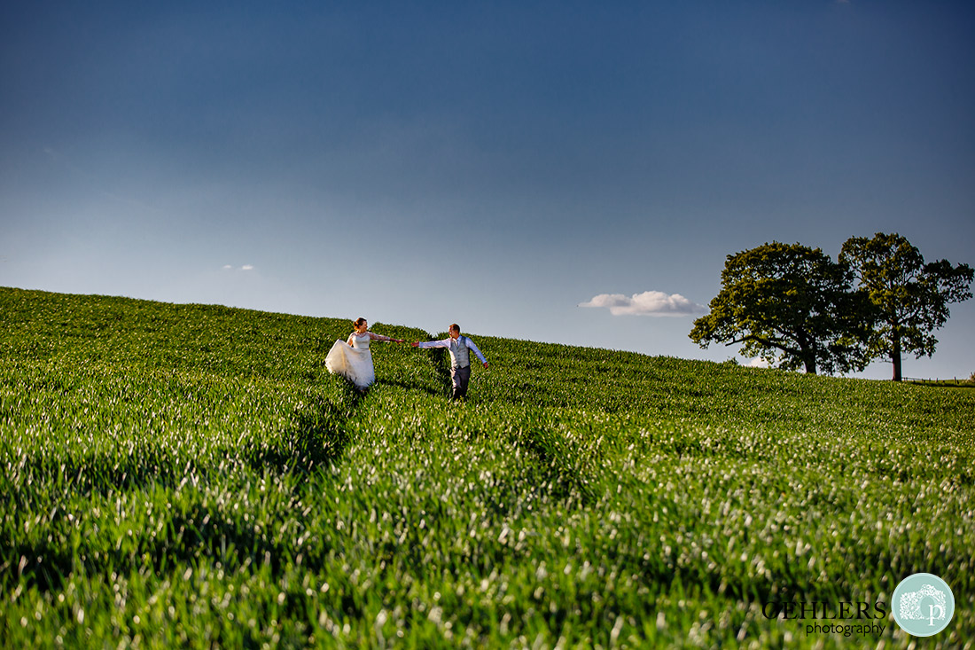 Kedleston Country House Photographers - bride and groom walking down the paths of the field towards the camera.