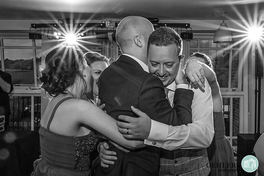 Friends hugging the groom on the dance floor.
