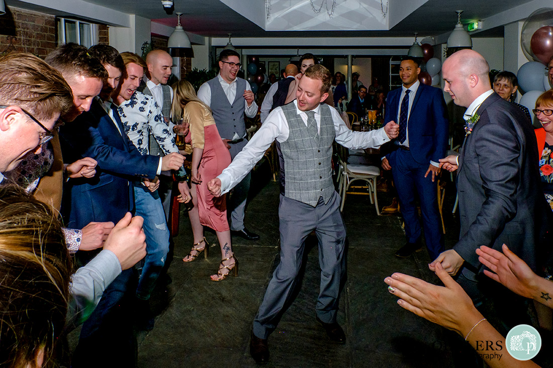 Groom dancing on the dancefloor surrounded by friends.