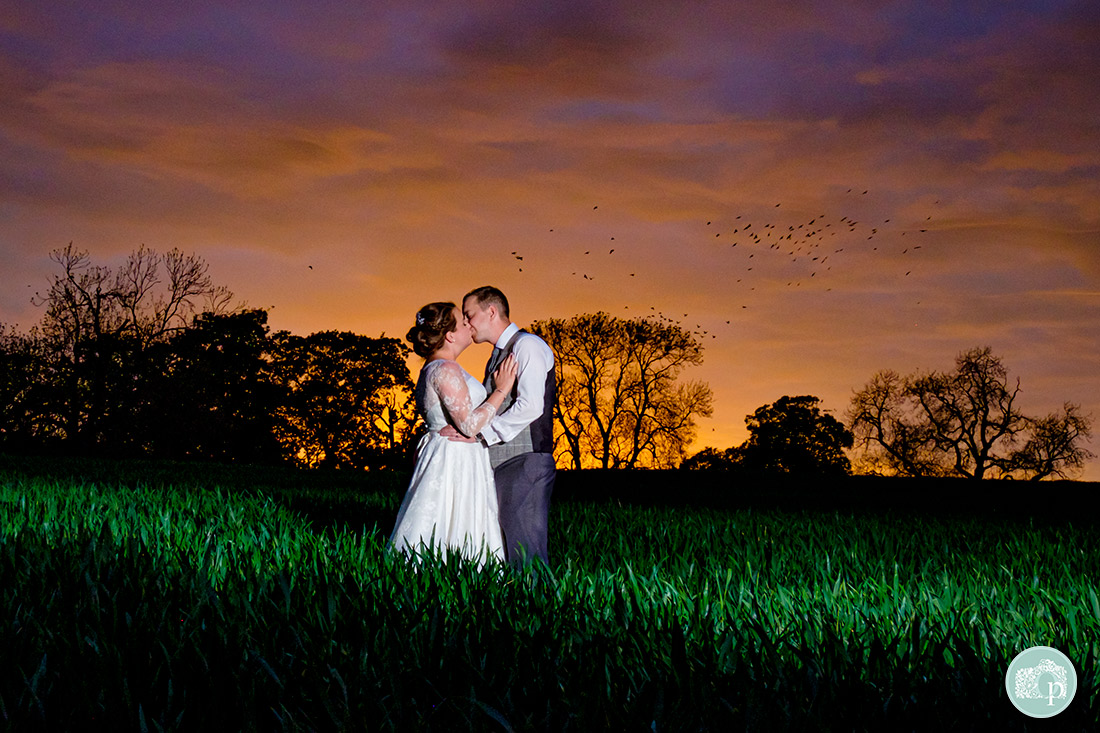 Kedleston Country House Photographers - beautiful sunset photograph of the bride and groom in a field with birds in the background.