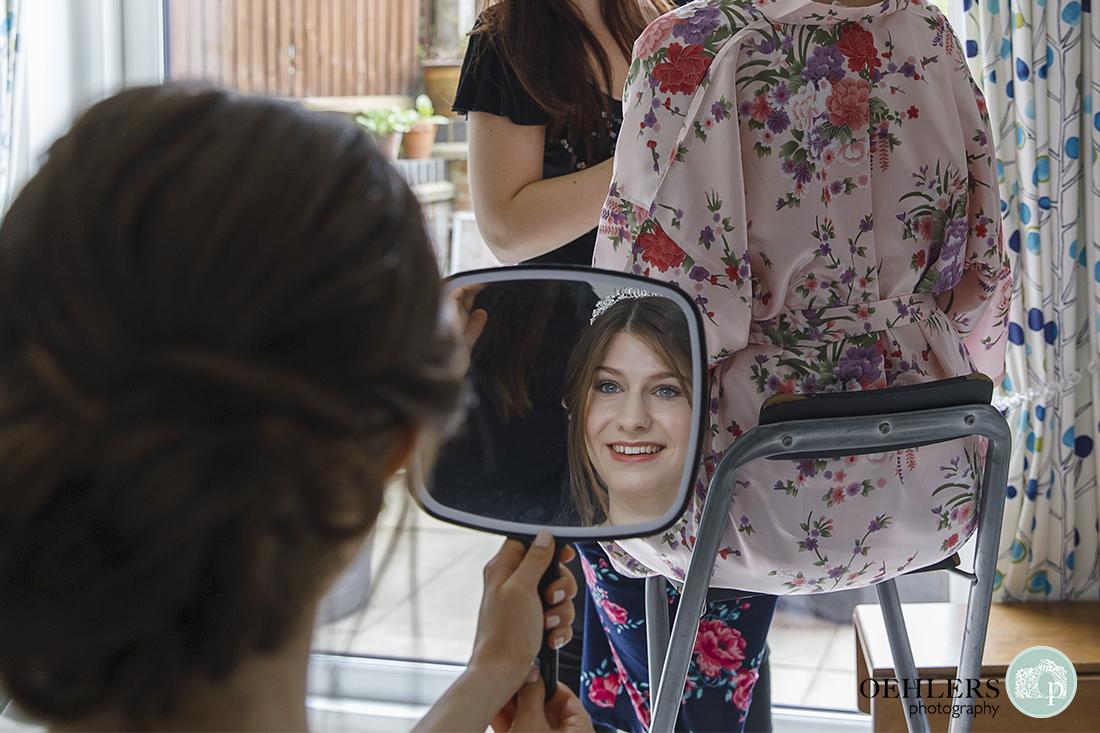 Bride looking at herself in a handheld mirror.