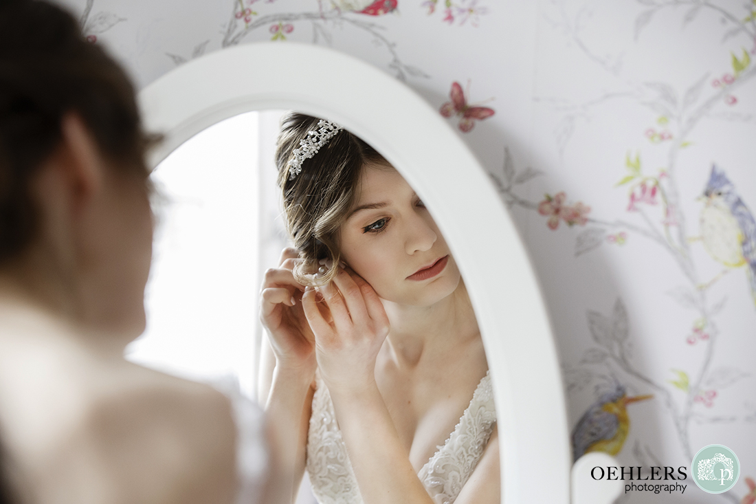 Beautiful reflection of the bride putting on her earring in the mirror.
