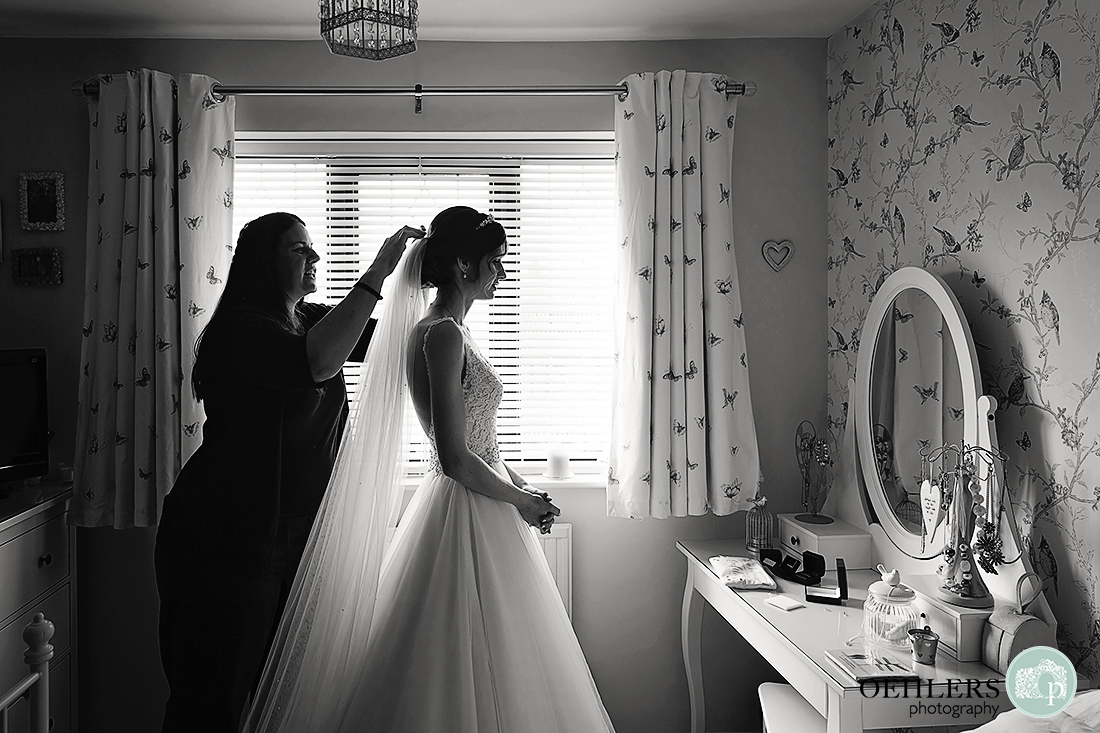Black and white partial silhouetted picture of bride having her veil put on.