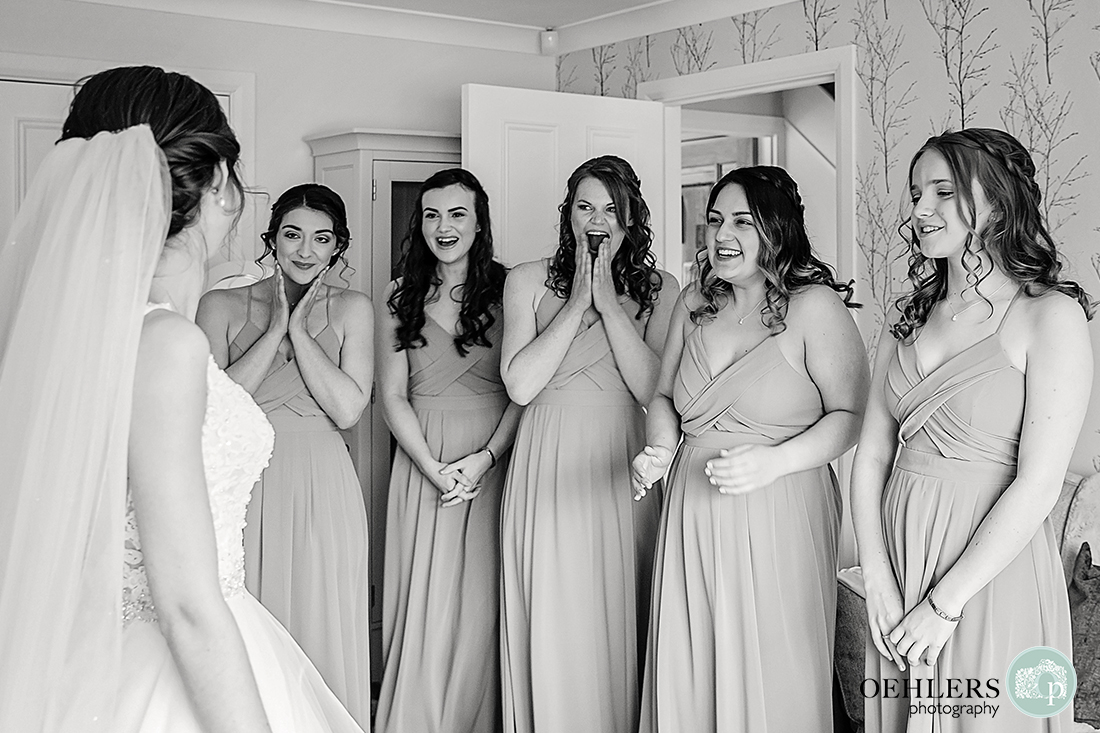 Emotional bridesmaids see their bride for the first time in her dress.
