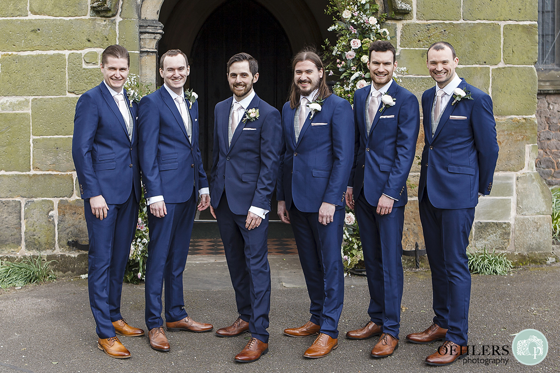 Groomsmen posing for a shot in front of the Holy Trinity Church.