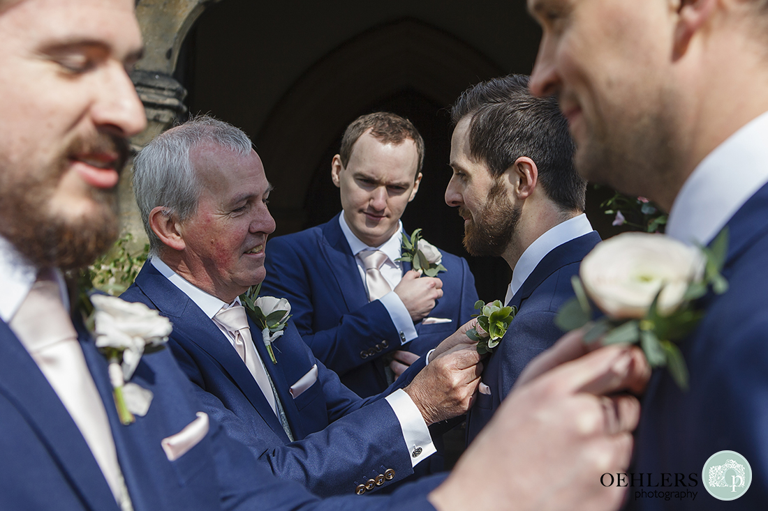 Groomsmen helping each other put on their button holes.