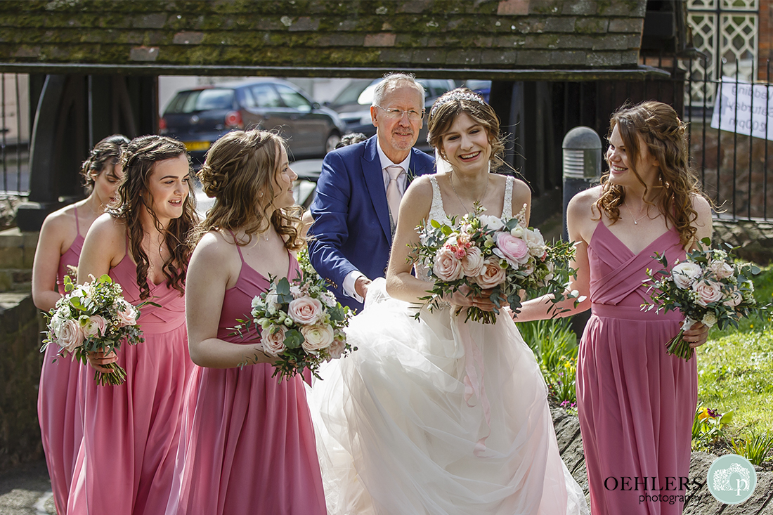 Bride with her dad and bridesmaids walking up to the Holy Trinity Church, Barrow upon Soar.