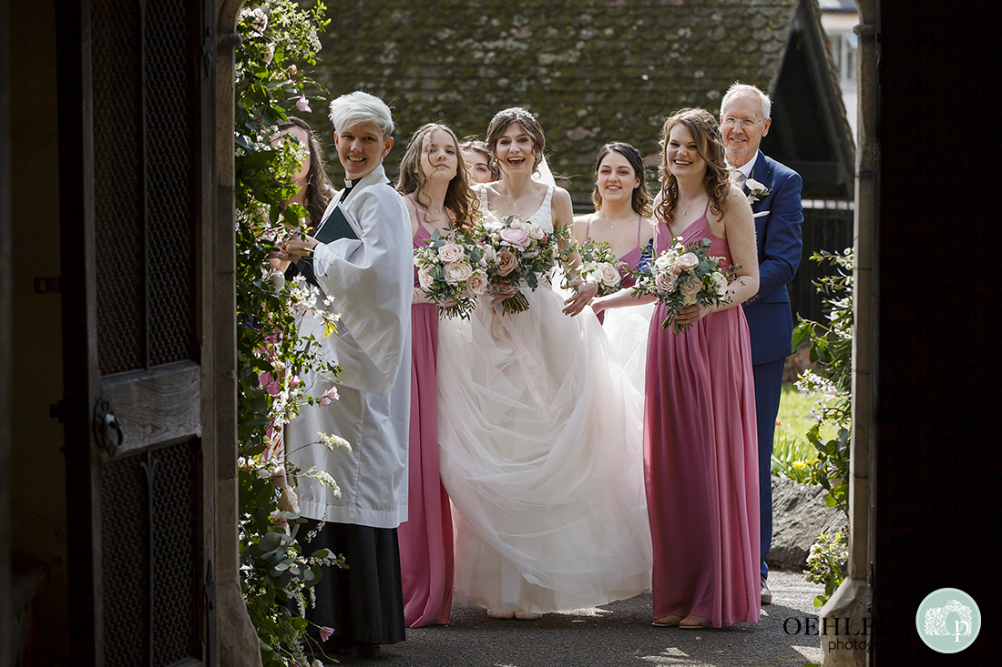 Bride waiting with anticipation with dad, bridesmaids and vicar outside the church doorway.