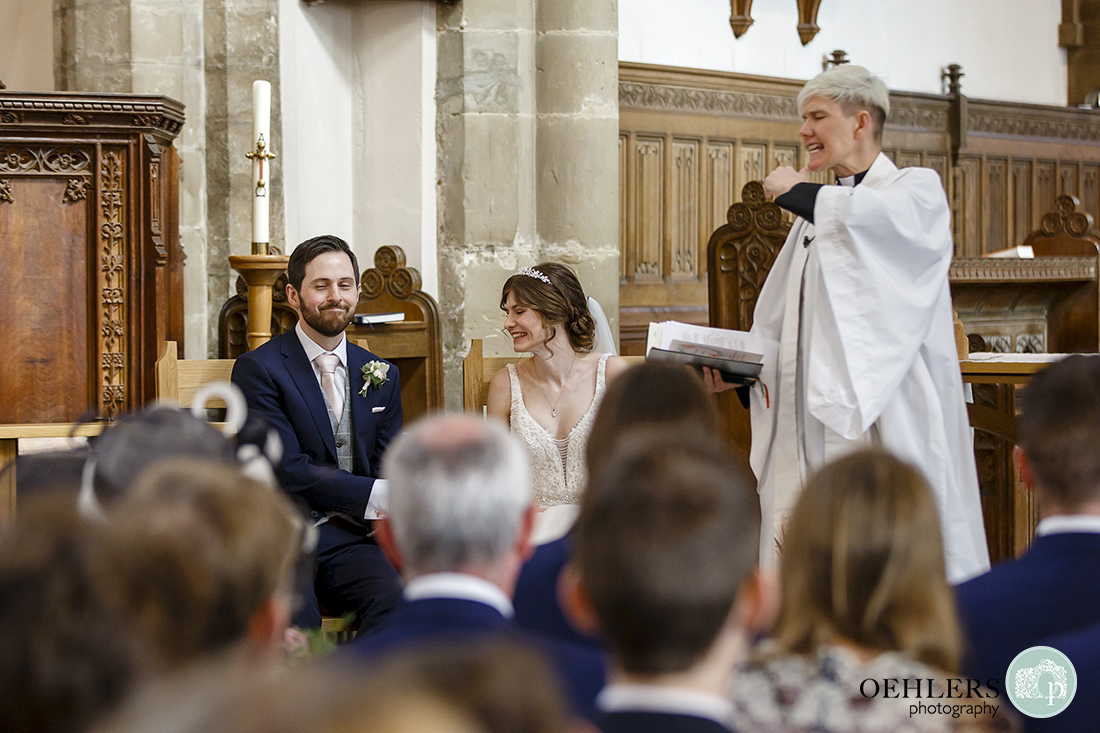 Animated vicar says something about the groom that makes him smirk.