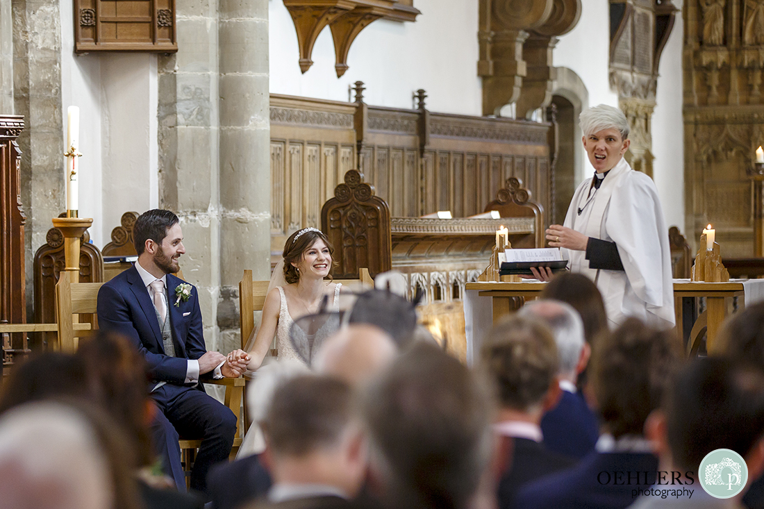 Animated vicar makes the bride and groom laugh.