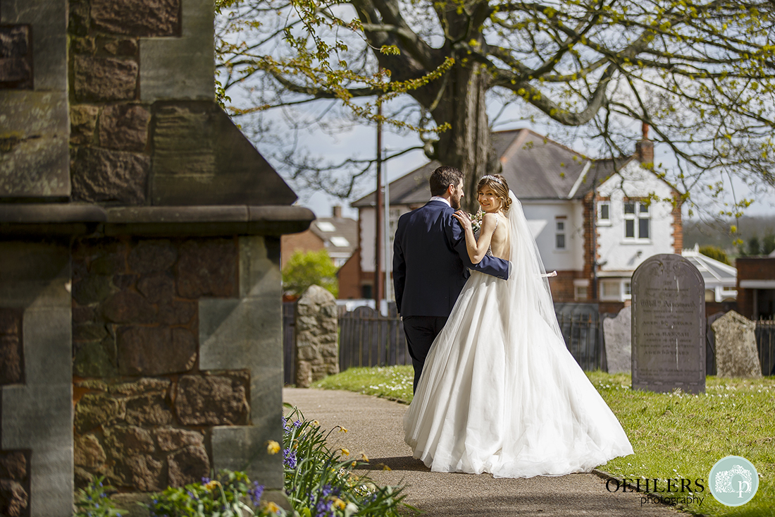 Bride and Groom walk around the corner of the church. The bride looking back at the camera whilst the groom looks at her.