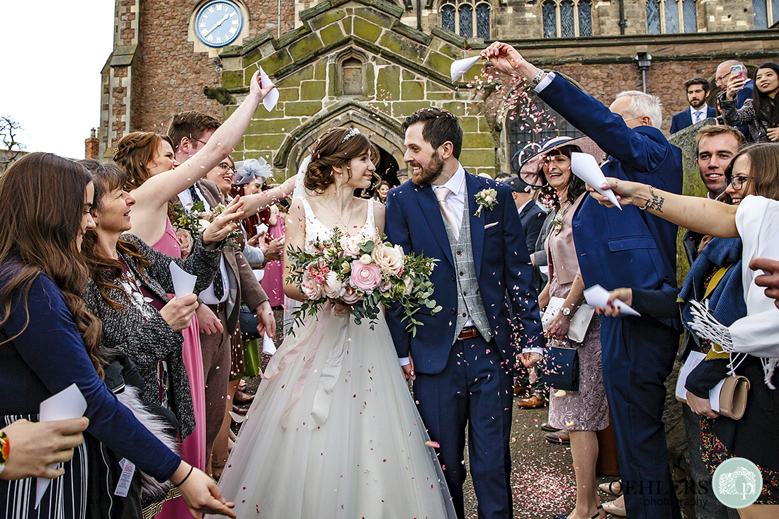 Lots of confetti being thrown whilst Bride and Groom look at each other and walk down the pathway away from the church.