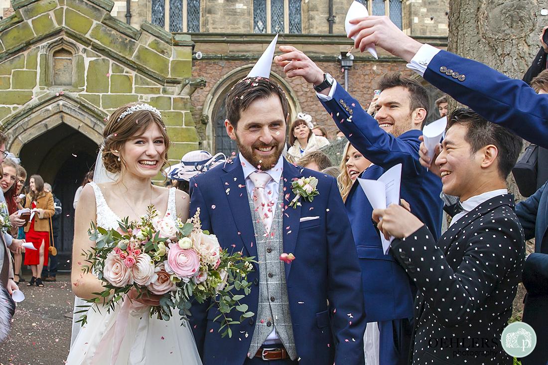Groomsman puts a confetti cone on the groom's head.