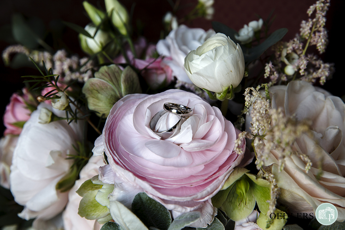 Wedding rings on the top of a flower in the wedding bouquet.