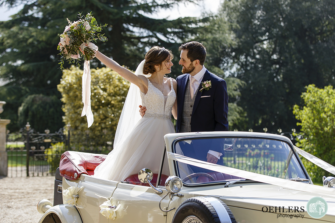 Bride and Groom stand in their wedding car at the entrance to the fabulous Prestwold Hall in Loughborough.