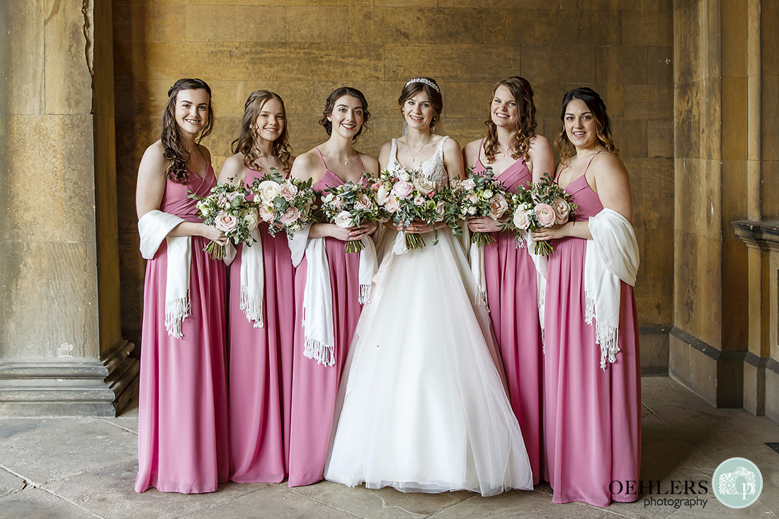 Bride with her bridesmaids posing for a photograph in the entrance to Prestwold Hall.