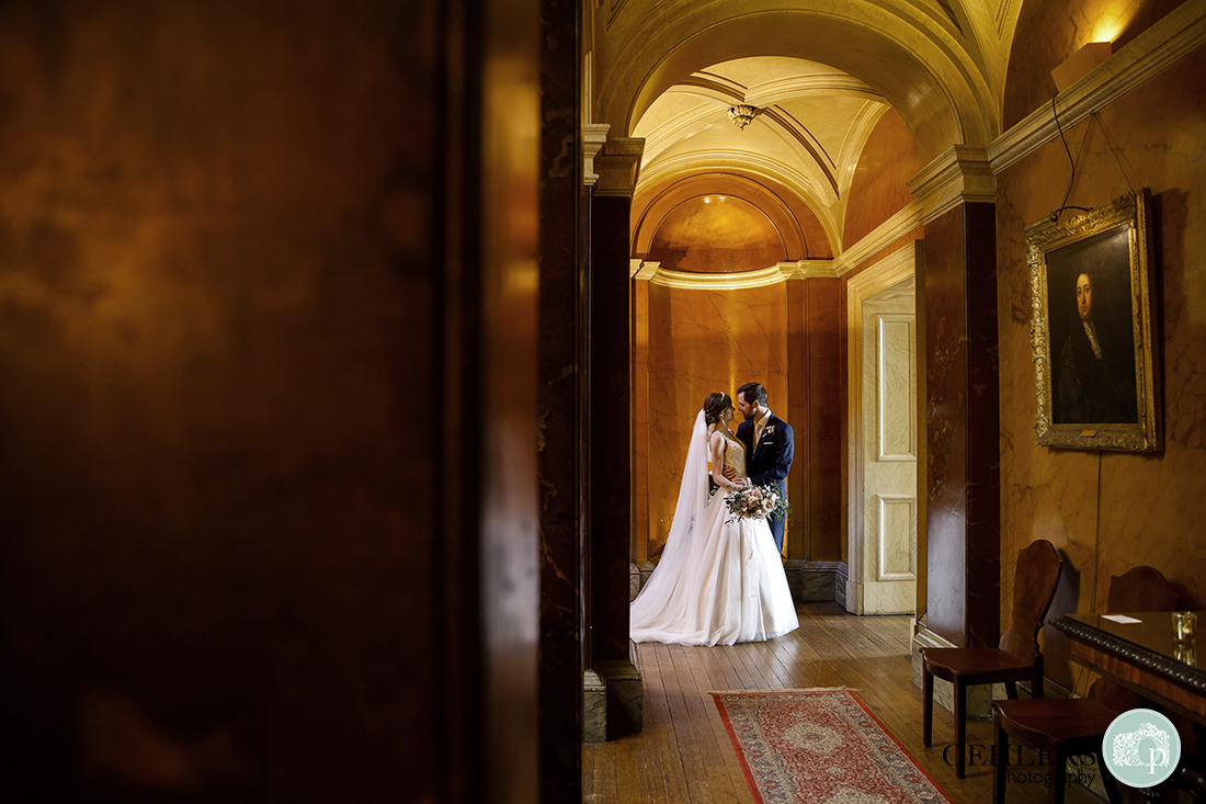 A beautiful photograph of the bride and groom inside the hallway of Prestwold Hall.