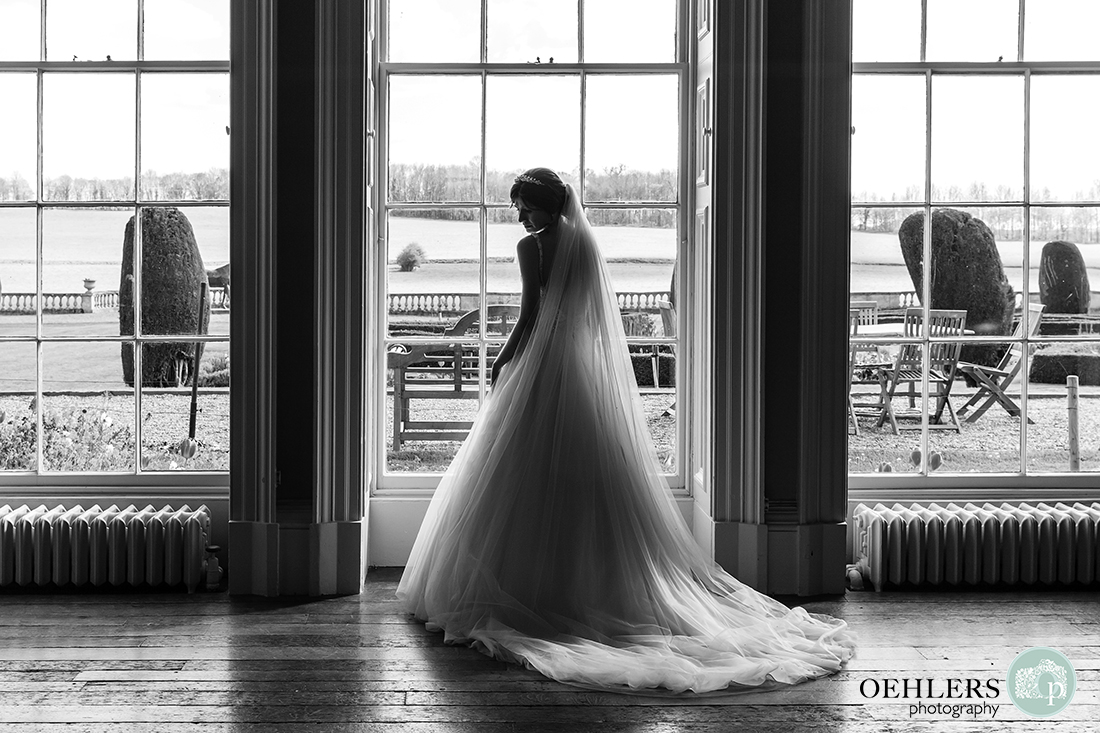 A Black and White image of the beautiful bride silhouetted in front of a lit window in the library of Prestwold Hall.