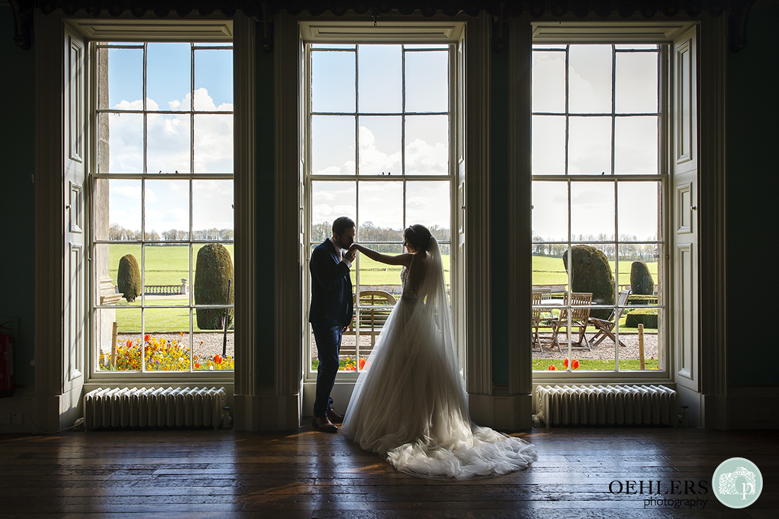 The groom kissing the brides hand in front of the window in the library of Prestwold Hall.