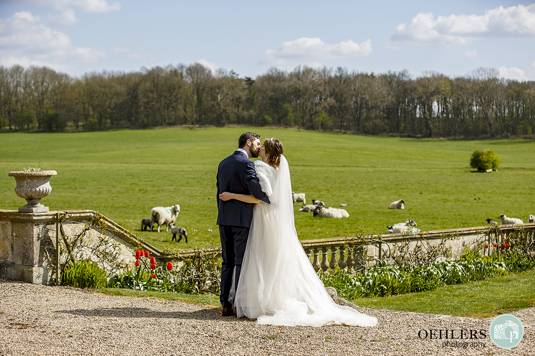 Beautiful countryside at Prestwold Hall with the bride and groom kissing.