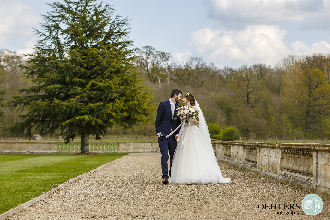 Bride and groom walking down the pathway in the gardens of Prestwold Hall.
