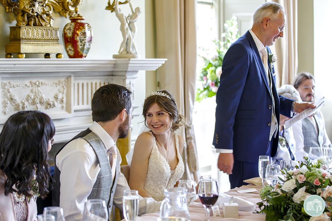 Speeches - Bride looking at her groom whilst her dad says his speech.