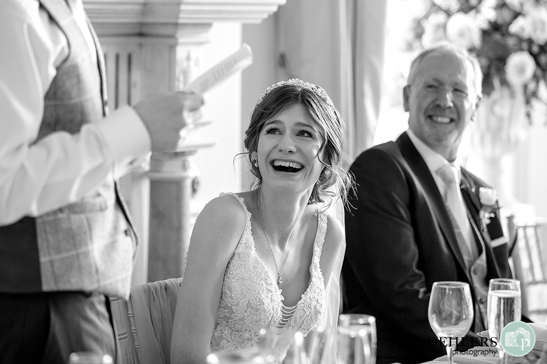 Bride laughs at something the groom said in his speech.