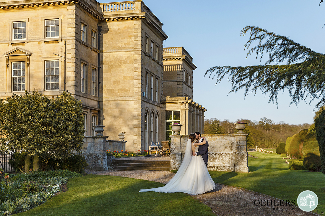 Bride and Groom having a romantic kiss in the garden of Prestwold Hall.
