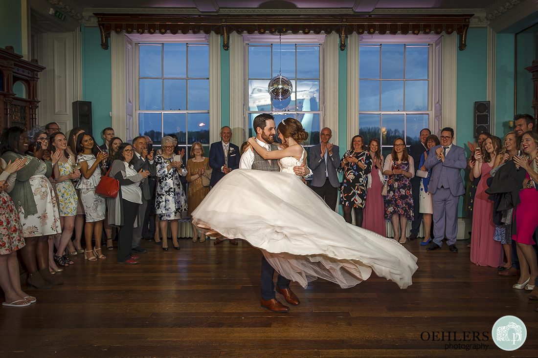 Groom picks up his bride and twirls her around on the dance floor in the library at Prestwold Hall.