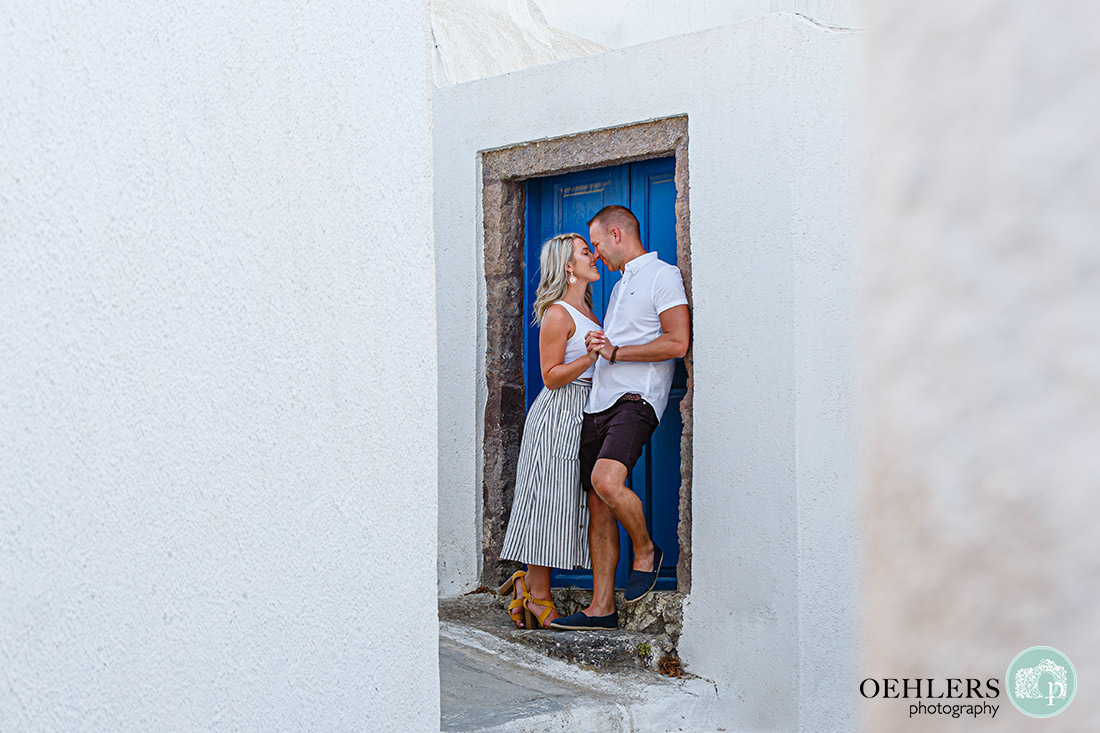 Santorini Wedding Photographers - Couple about to kiss in front of a blue door.