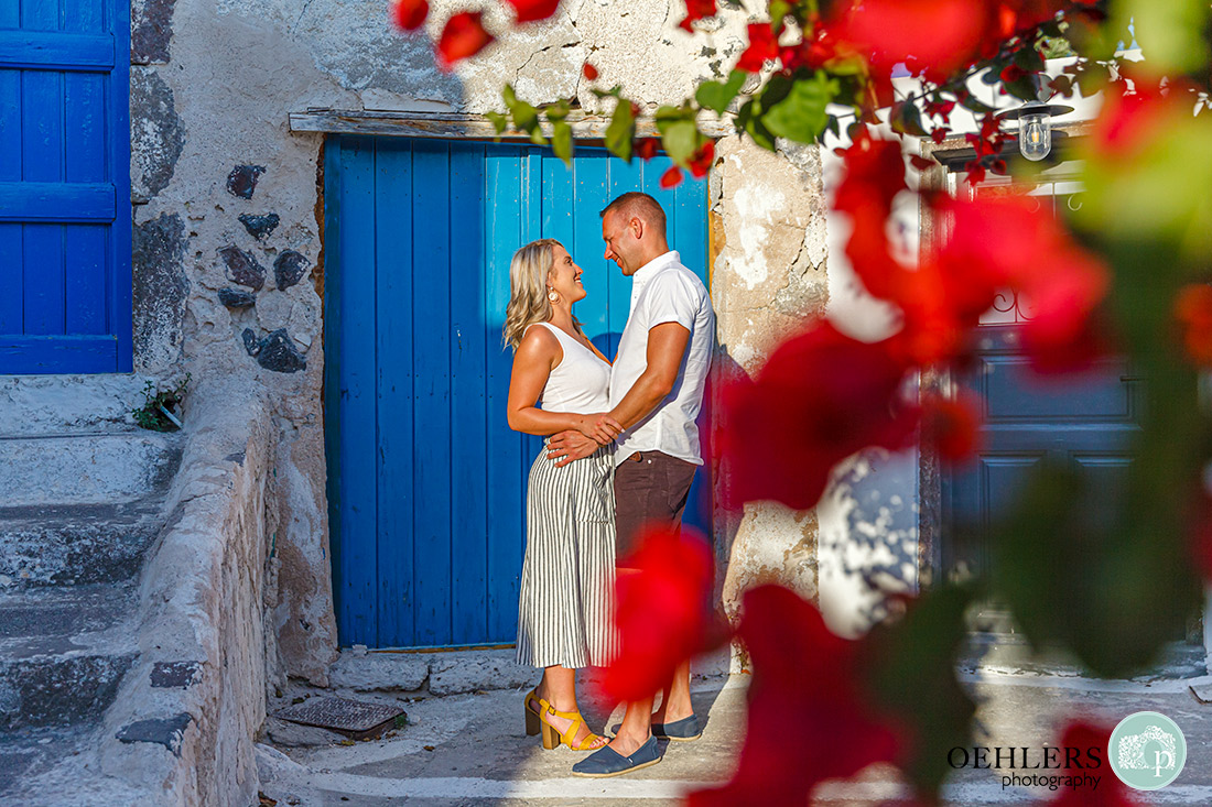 Santorini Wedding Photographers - shoot through bougainvillea to couple in front of blue door in the sunshine.