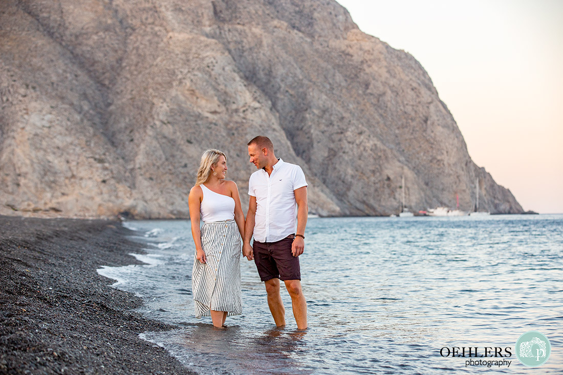 A romantic walk on the volcanic beach of Perissa, Santorini.