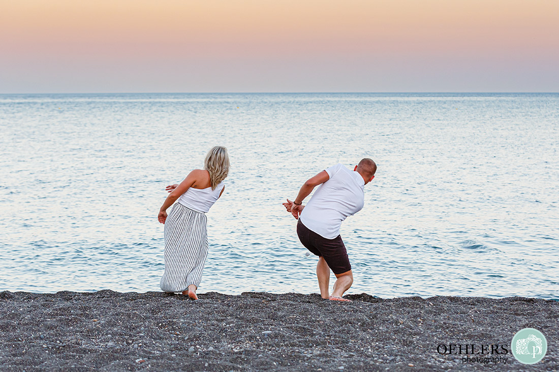 Santorini Wedding Photographers - couple skimming stones on Perissa Beach, Santorini.