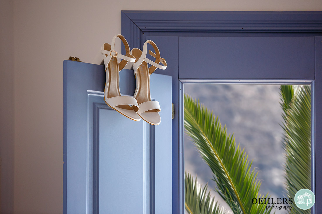 Santorini Wedding Photographers - wedding shoes hanging on blue door of bedroom with palm tree in the background.