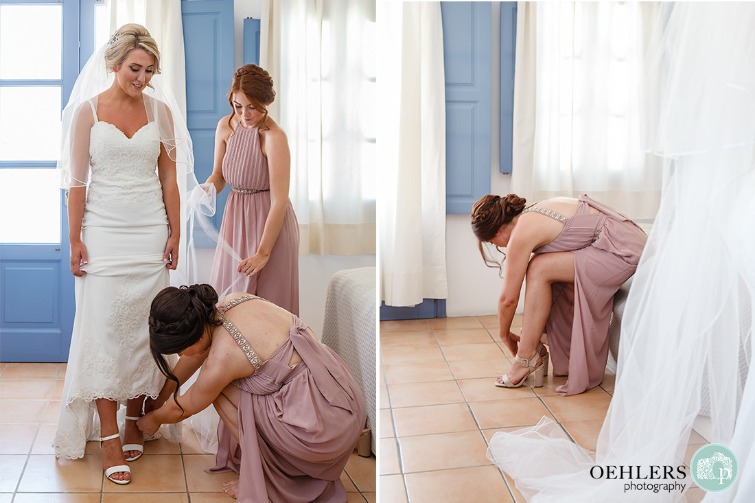 Bridesmaids dressing the bride as well as a bridesmaid putting on her shoes.