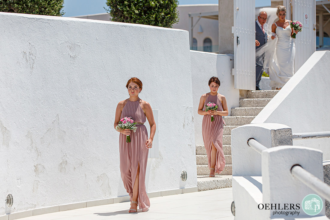 Santorini Destination Wedding Photographers - bridesmaids and bride and dad entering the ceremony area.