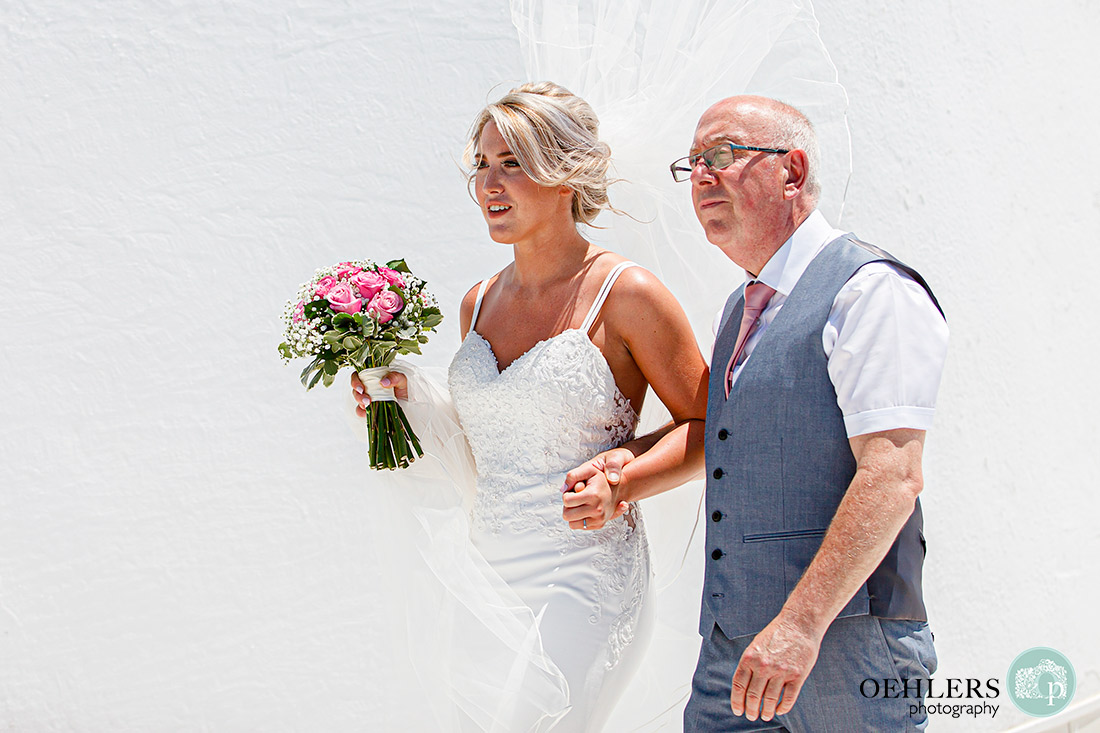 Santorini Destination Wedding Photographers - bride and dad walking eagerly towards the groom.