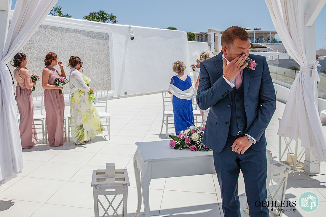 Santorini Destination Wedding Photographers - after spotting his bride, the groom emotionally wipes a tear from his eyes.