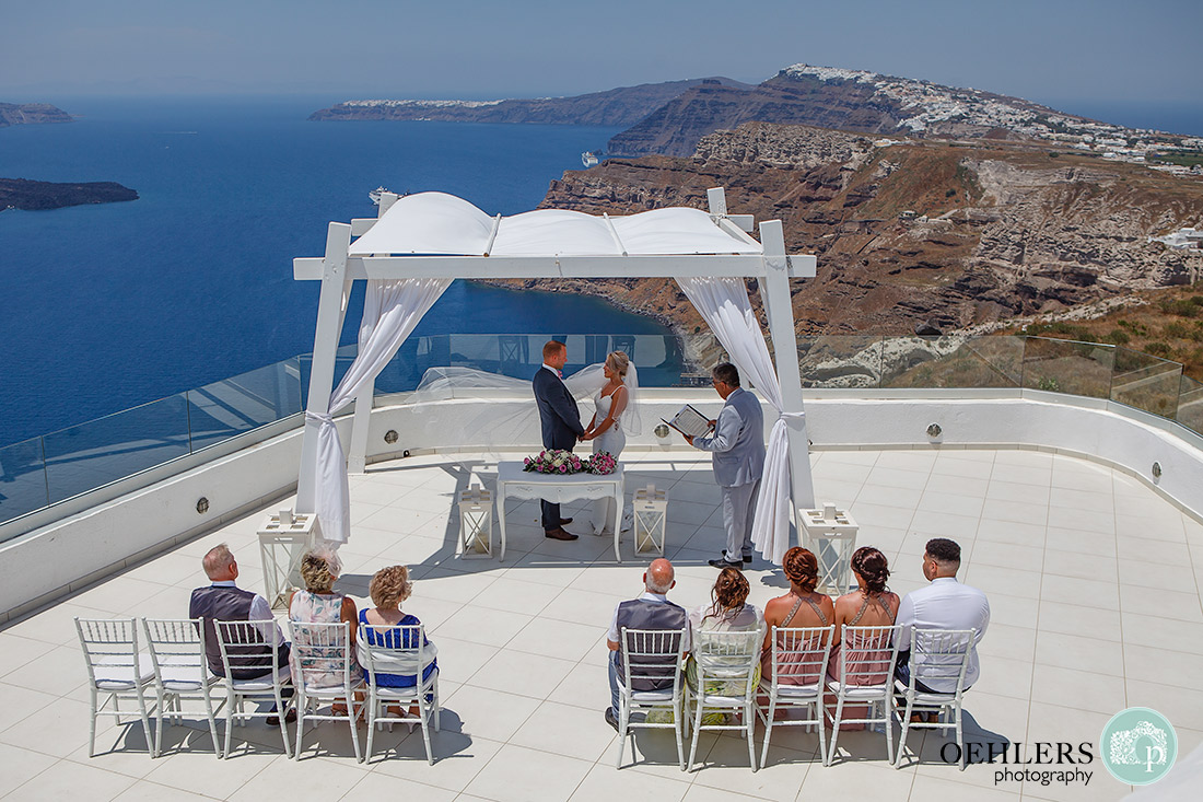 Santorini Destination Wedding Photographers - wow what a backdrop to the ceremony area of the caldera and Aegean Sea.