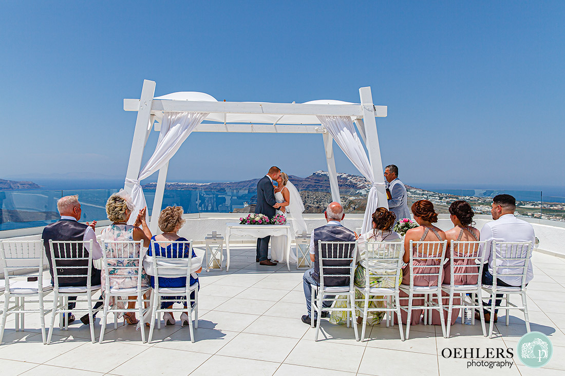 Santorini Destination Wedding Photographers - the first kiss as husband and bride under the canopy of the ceremony structure.